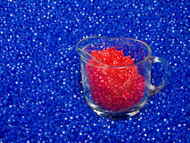 Colored Beads. Red and Blue Plastic Colored Beads with glass measuring cup Stock Photo
