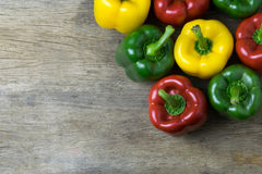 Colored bell peppers on wooden table Royalty Free Stock Photos