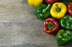 Colored bell peppers on wooden table Royalty Free Stock Images