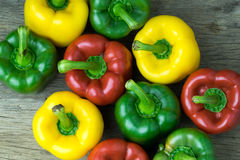 Colored bell peppers on wooden table Stock Photography