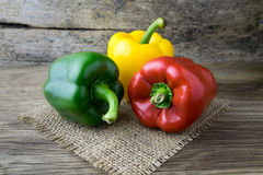Colored bell peppers on wooden table Royalty Free Stock Photo