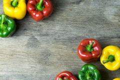 Colored bell peppers on wooden table Stock Image