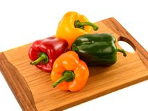 Colored bell peppers on wooden table Stock Images