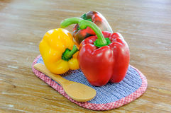 Colored bell peppers on wooden table Royalty Free Stock Photography