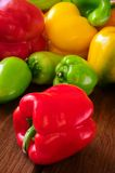 Colored bell peppers on wooden table Stock Photos