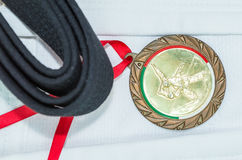 Colored belts in martial arts, and a part of judo uniform. Colored belts in martial arts, part of judo uniform and a medal, for an almost abstract background Stock Photography