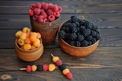 Colored berries of red, yellow and black raspberries or blackberries in earthenware on a  table royalty free stock photo