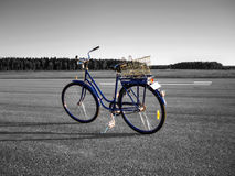 Colored bicycle, monochrome background. Blue bicycle with monochrome background standing at airbase runway Stock Image