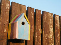 Colored birdhouse on a fence Royalty Free Stock Image
