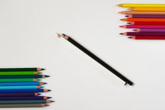 Colored, black and white pencils on the contrary. Royalty Free Stock Photo