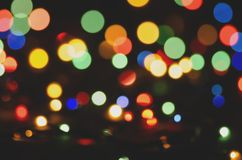 Colored blurred lights on dark background. Bokeh, soft focus stock images