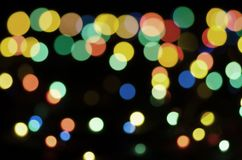 Colored blurry lights on a black background. Bokeh, soft focus royalty free stock photos