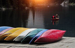 Colored boats on the dock. Colorful fiberglass kayaks tethered to a dock as seen from above Stock Photo