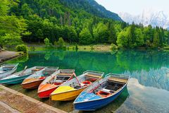 Colored Boats at lake of mountain. Italy stock photo