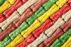 Colored bone shaped dog treats background. Background of bone shaped dog treats in different colors and flavours Stock Image