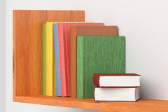 Colored books on wooden bookshelf on white wall Stock Photo
