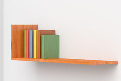 Colored books on wooden bookshelf on white wall Royalty Free Stock Photo