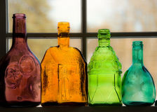 Colored Bottles. Colored glass bottles aligned on a windowsill royalty free stock photo