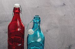 Colored bottles, blue and red glass with a cogged stopper on the neck, on a wooden tabletop.  stock photography