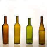 Colored bottles with and without water Royalty Free Stock Images