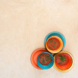 Colored bowls with tomato gazpacho soup on a wooden surface Stock Photography
