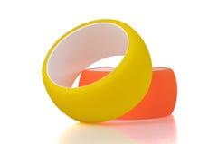 Colored bracelets. Yellow and orange polymer bracelets on white background Royalty Free Stock Photography