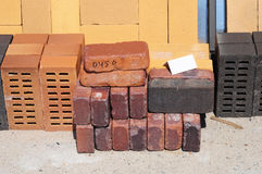 Colored building blocks, bricks and concrete pavers (paving stone) or patio blocks organized on pallets for sale stock images