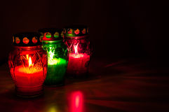 Colored burning votive candles in the dark Stock Image
