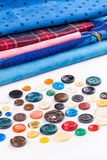 Colored buttons and cloth on white background Royalty Free Stock Photo