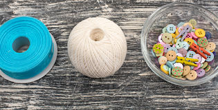 Colored buttons in glass Cup on old wooden Board. Materials for creativity and Hobbies Stock Photo