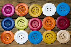 Colored buttons on wooden board, Colorful buttons, on old wooden Royalty Free Stock Image