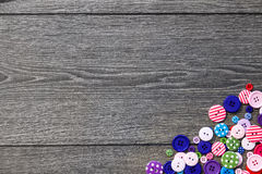 Colored buttons on wooden board. Colorful buttons, on old wooden texture background Stock Photo