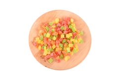 Colored candid fruit on wooden plate isolated Stock Photography
