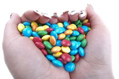 Colored candies in hands Stock Image