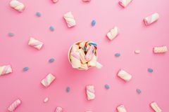 Colored candies and marshmallow with cappuccino mug on pink background. Flat lay, top view. Rainbow sugar cane in mug with coffee Royalty Free Stock Photography