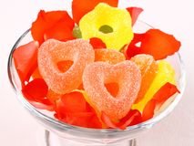 Colored candies with two red hearts in glass bowl and rose petals Royalty Free Stock Photos