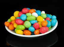 Colored candies in white saucer Stock Photos