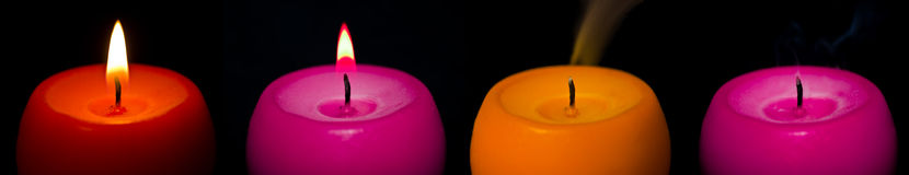 Colored candles. Different colors candles isolated on black background, with flame fading Stock Image