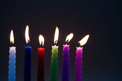 Colored candles on black background. six pieces. each candle silhouette with real flame. Light and darkness concept Stock Images