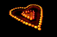 Colored candles lighted in heart form Royalty Free Stock Photos