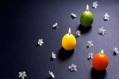 Colored candles in the shape of Easter egg with flowers on black Royalty Free Stock Photos