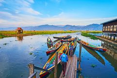 Colored canoes in wharf, Ywama, Inle Lake, Myanmar. YWAMA, MYANMAR - FEBRUARY 18, 2018: The colored kayaks in wharf of Nga Phe Chaung Monastery of jumping cats Stock Photo