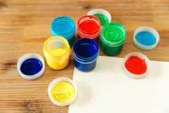 Colored cans with paint and paper.wooden table. stock photography