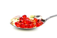 Colored capsules with vitamins in a spoonful. Royalty Free Stock Photos