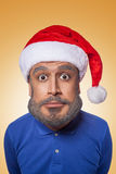 The colored caricature of the funny santa clause with big head and blue shirt, red hat with gray beard, surprised looking. At camera on orange background.nyoung Royalty Free Stock Image