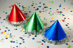 Colored Carnival Hats. Red Blue and Green hats on confetti background Stock Photos
