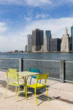 The colored chairs in front of the buildings of Manhattan and east river Royalty Free Stock Images