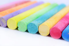 Colored chalk arranged on a white background Royalty Free Stock Images