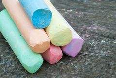Colored chalk for drawing on a wooden background stock photos