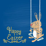 Colored chalk drawn illustration for Easter with rabbit on a swing and golden text. Happy Easter theme. Stock Photo